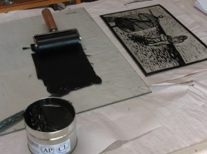 Inking up the lino block for printing.